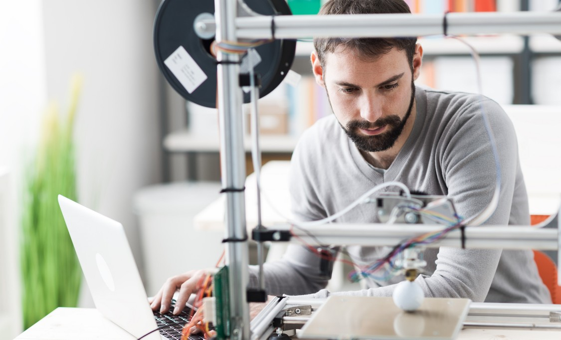 Young designer engineer using a 3D printer in the laboratory and studying a product prototype, technology and innovation concept
