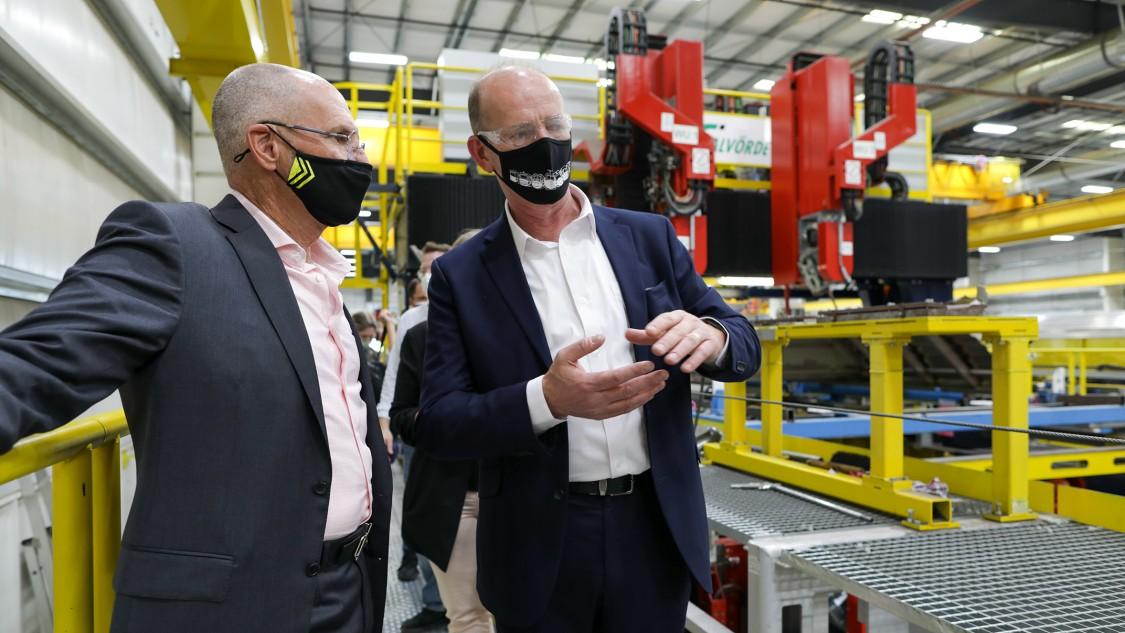 Image of two men in masks talking