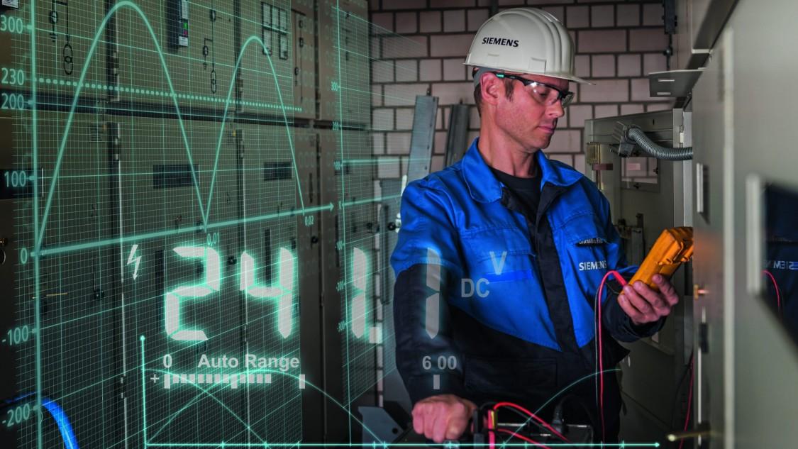 homem utilizando epi mendindo energia elétrica com equipamentos siemens com filtros azuis mostrando a voltagem do sistema