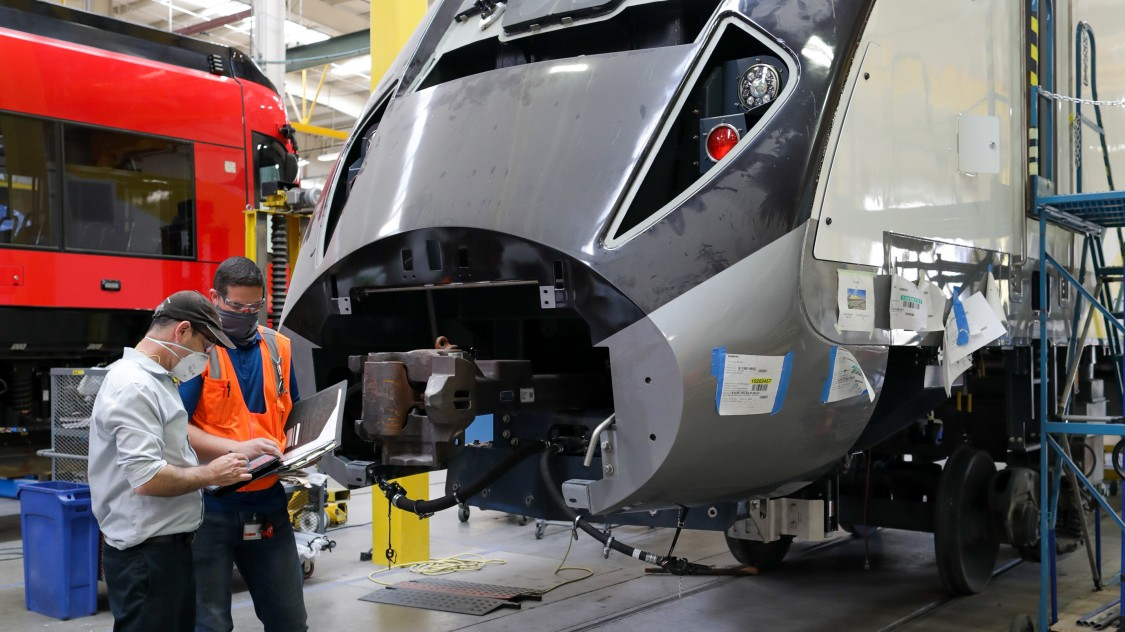 People lokoing at a train being made in the Sacremento Facility