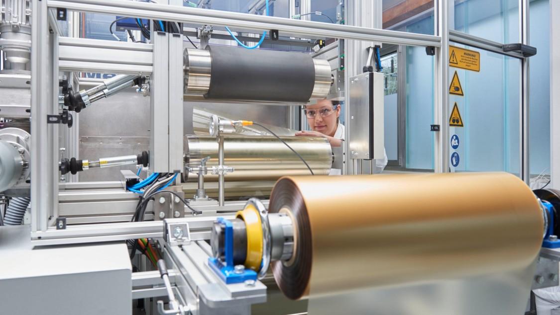 Blick in Power-to-Gas-Anlage mit einer prominenten Walze im Vordergrund. Im Hintergrund ist eine Frau, die den Prozess der Wasserstoff-Elektrolyse beobachtet.