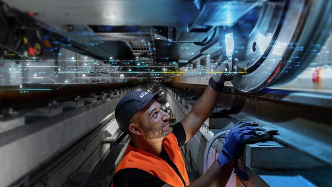 Servicetechniker von Siemens Mobility Rail Services bei der Arbeit unter einem Schienenfahrzeug – überprüft das Laufrad