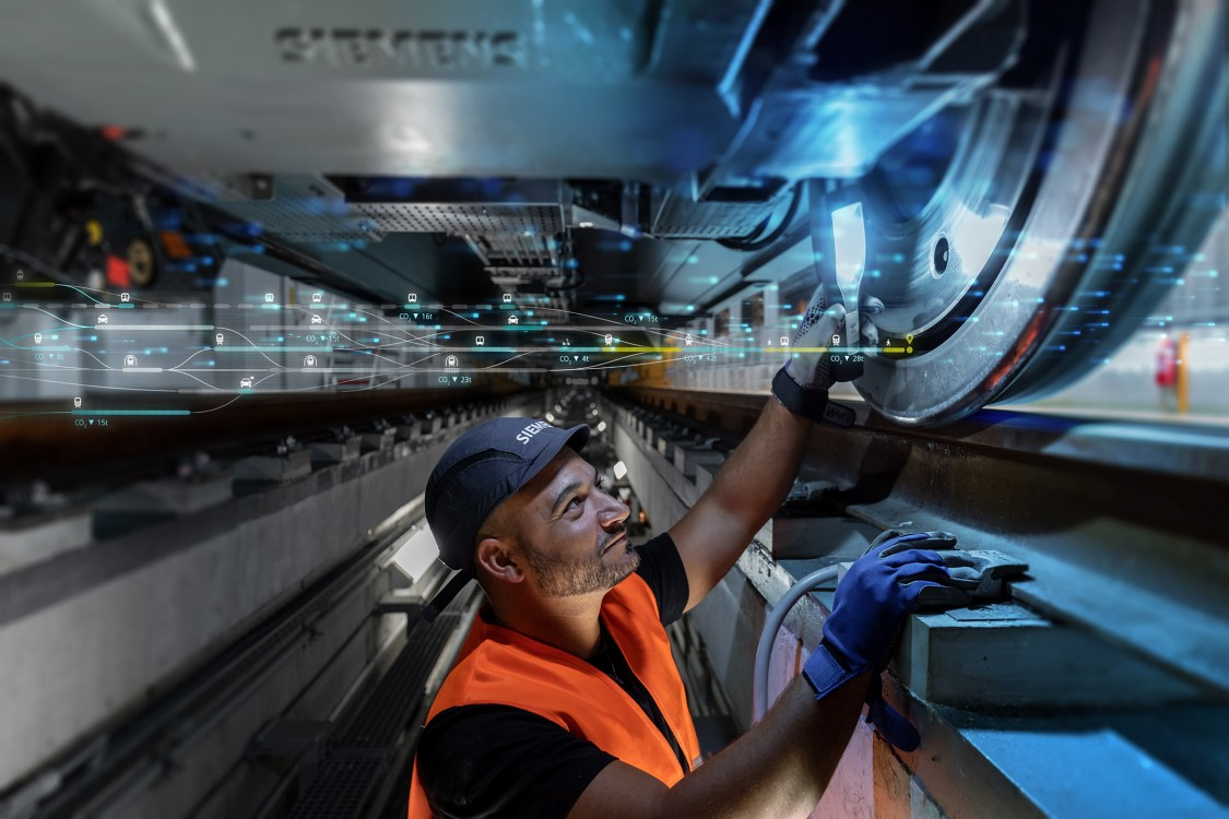Service technician from Siemens Mobility Rail Services at work beneath a rail vehicle – checks the track wheel