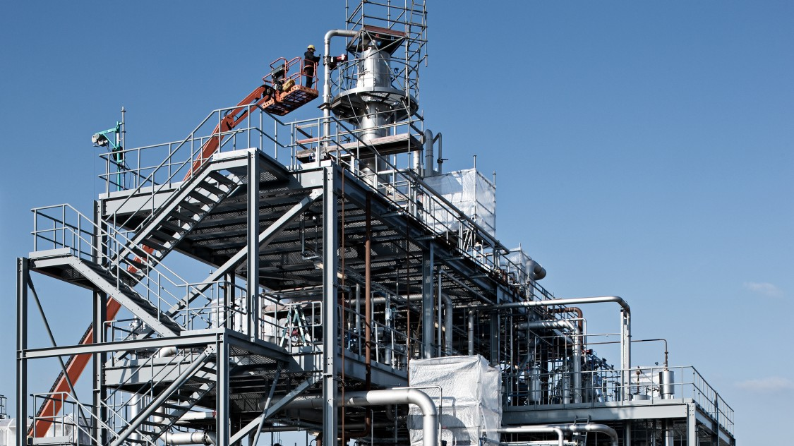 Bioethanol plant in three levels of pipes and railings with column in the middle, on which a man checks out or sets something out of a sickbay.