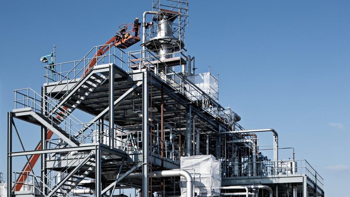 Bioethanol-Anlage in drei Etagen aus Rohren und Geländern mit Kolonne in der Mitte, an der ein Mann aus einem Krankorb heraus etwas prüft oder einstellt.