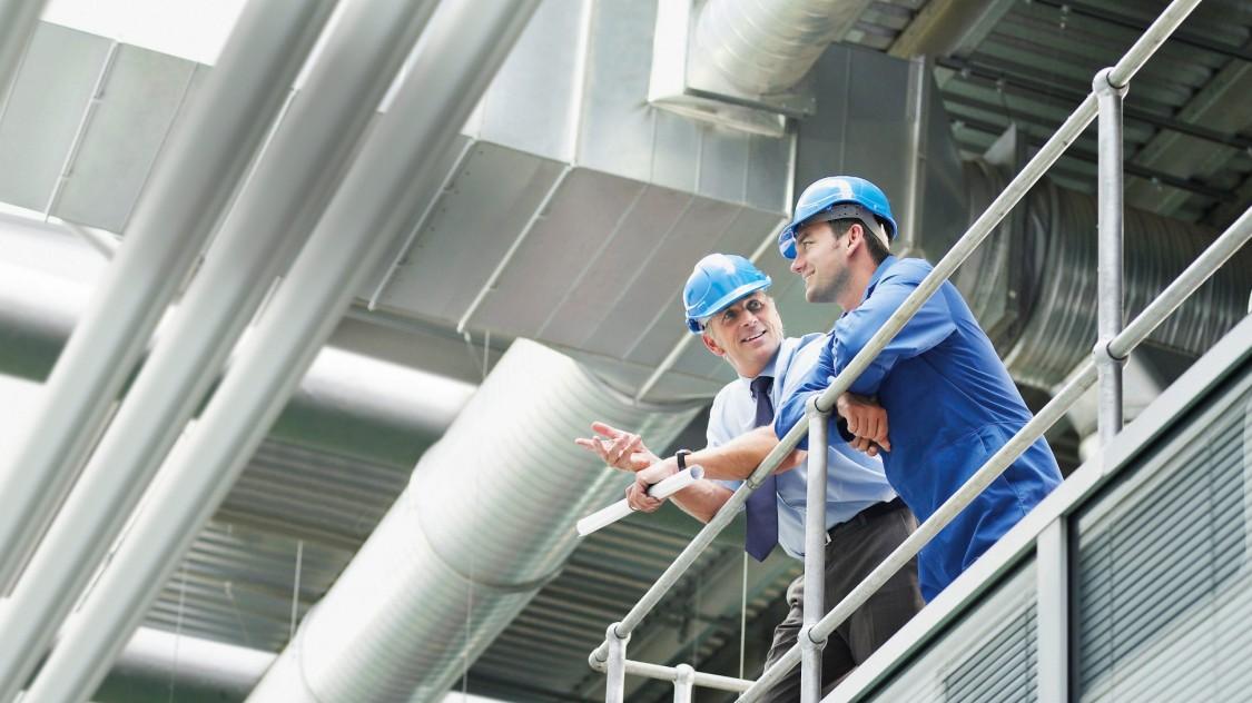 Manager und Techniker mit Schutzhelmen unterhalten sich im Werk