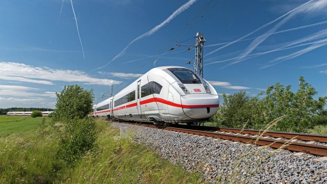 Bild des ICE 4 von Siemens Mobility in leichter Diagonalansicht bei der Fahrt durch eine grüne Landschaft.