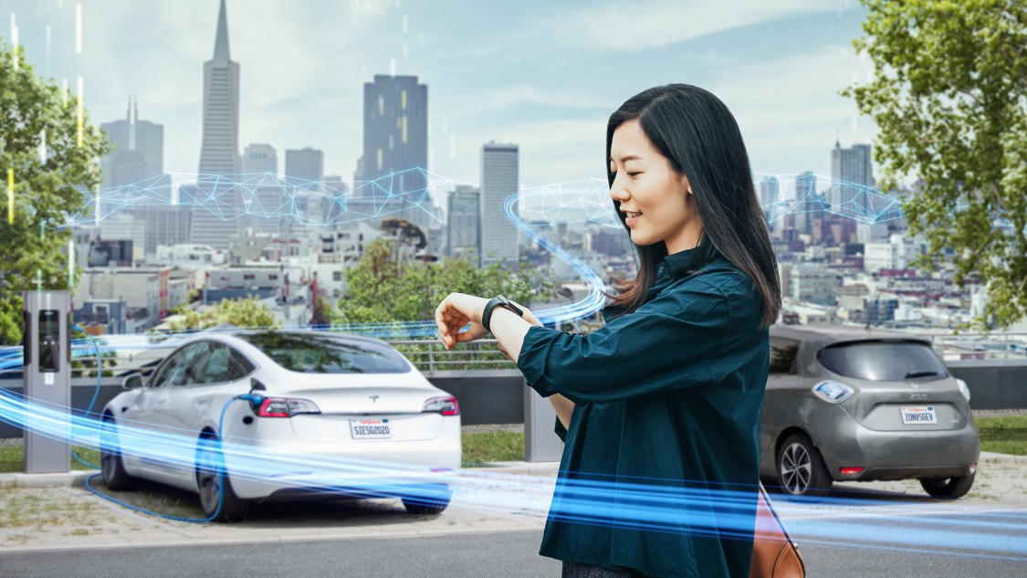 Smart infrastructure grid edge image with woman looking at her watch next to an electric car charging station
