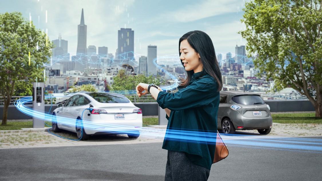 Frau die ein smart device mit ev Autos und Ladegeräten im Hintergrund betrachtet