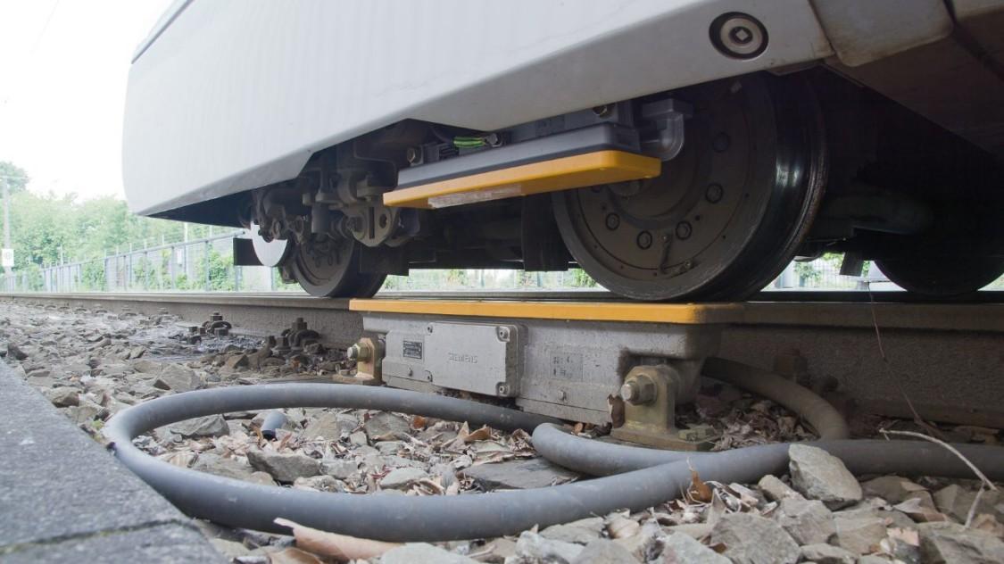 Zug fährt über ein streckenseitige Komponente für die Zugbeeinflussung