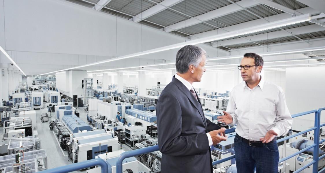 Dois executivos em uma fábrica cheia de computadores discutindo sobre os benefícios da digitalização