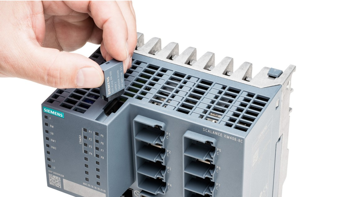 An hand holds a KEY-PLUG for Industrial Ethernet devices like the SCALANCE X-400 layer 2 switch