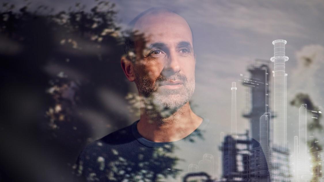 Frontalaufnahme eines Mannes hinter einer Glasscheibe, in der sich eine digitalisierte Darstellung einer chemischen Anlage und grüne Bäume spiegeln.