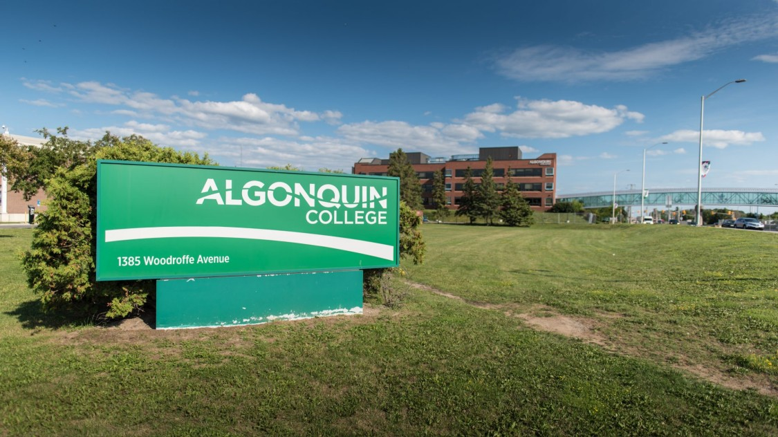 Algonquin College sign with building in campus background