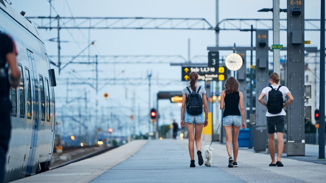 People walking on an outdoor train station platform