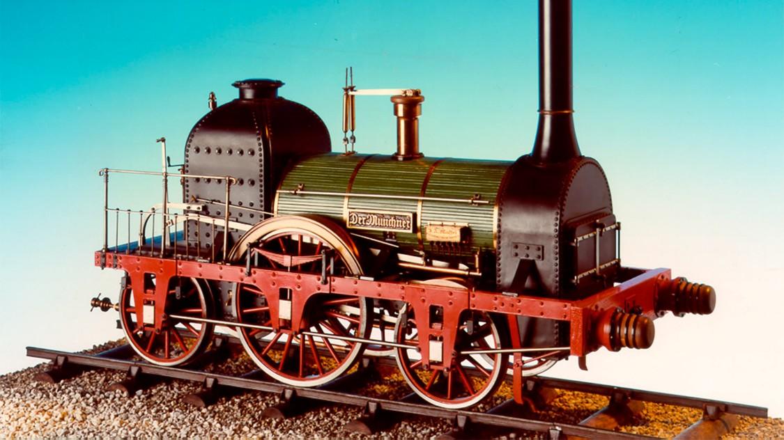 """Locomotivas foram construídas em Munique desde 1838. In 1841, J. A. Maffei fornece sua primeira locomotiva, com o nome """"Der Münchener."""" Em 1864, o número total de locomotivas entregues chega a 500, e no ano de 1900, a entrega da locomotiva número dois mil."""