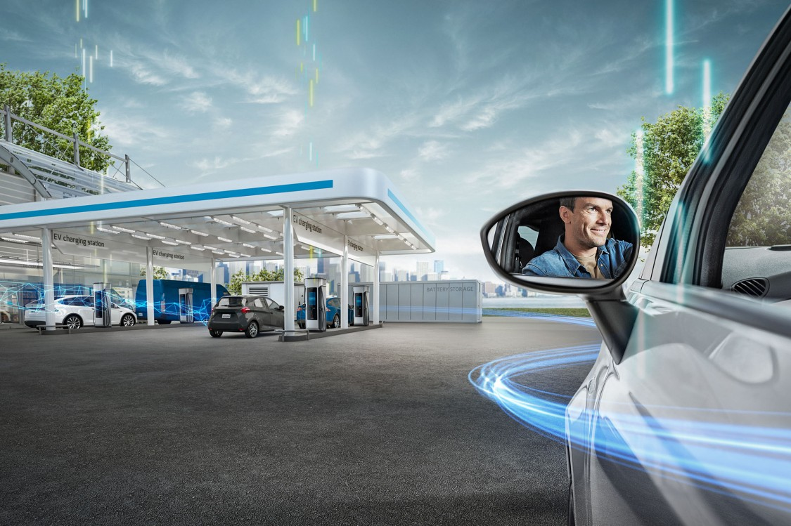 An EV approaches a state-of-the-art charging station. We see the driver in the side mirror.