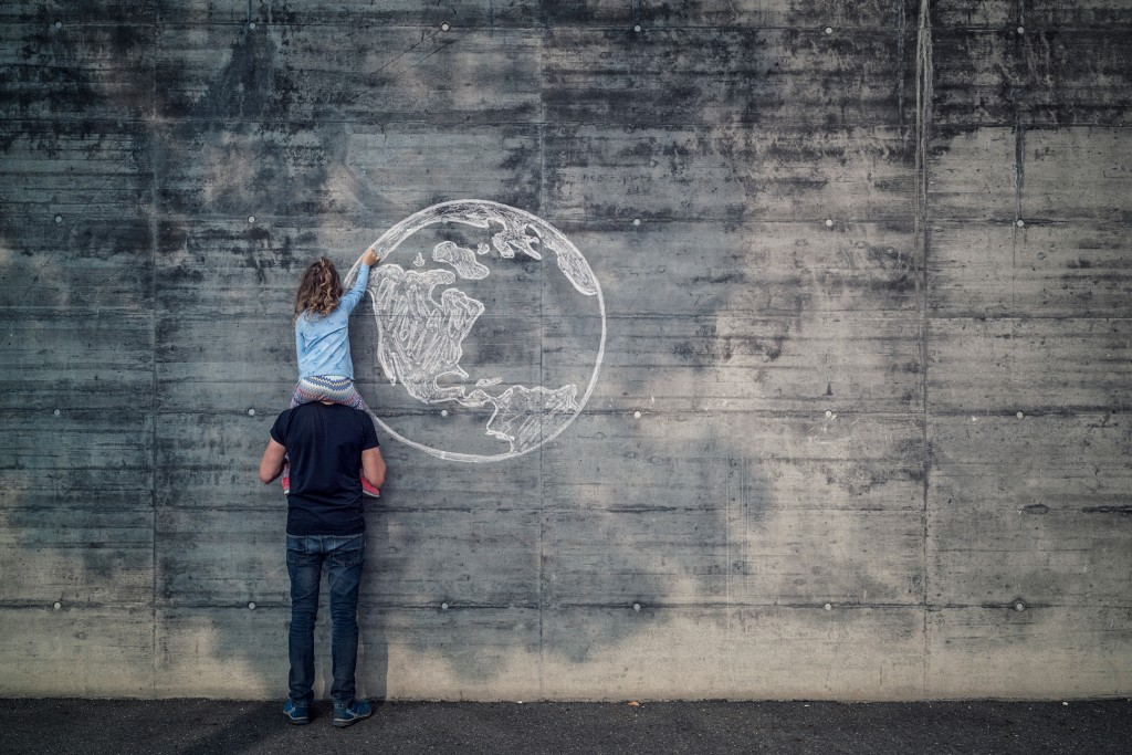 father-with-daughter-on-his-shoulders-the-daughter-drawing-the-earth-onto-a-concrete-wall-with-chalk-large.jpeg