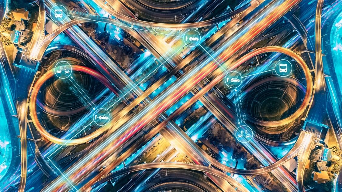 imagem aérea de vias de uma metrópole com rastros de luz dos carros em movimento representando a eletromobilidade