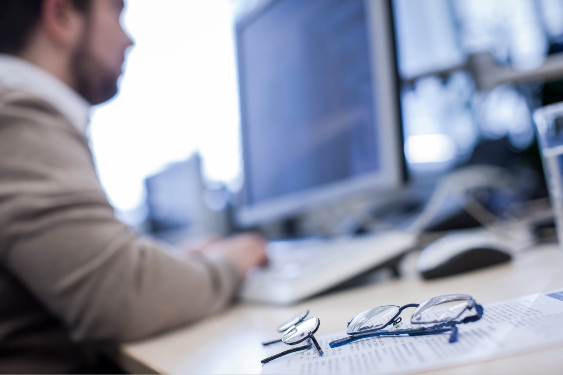 Stefano schaut konzentriert auf seinen Bildschirm, neben ihm liegt seine Brille