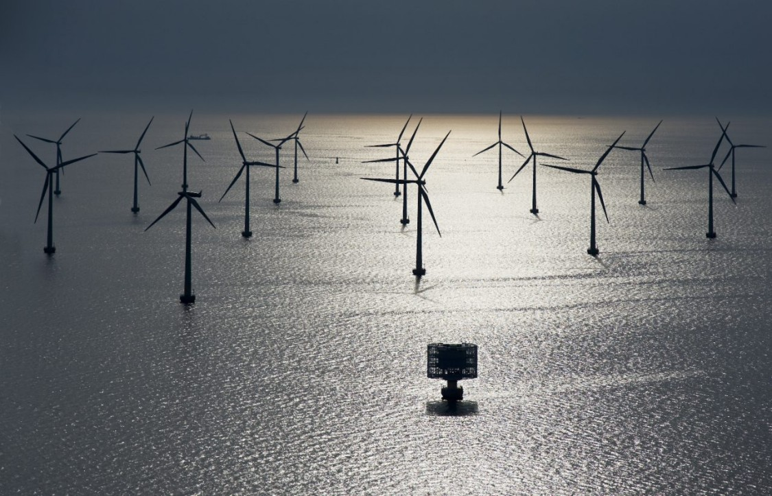 Wind turbines rising out of an early morning mist