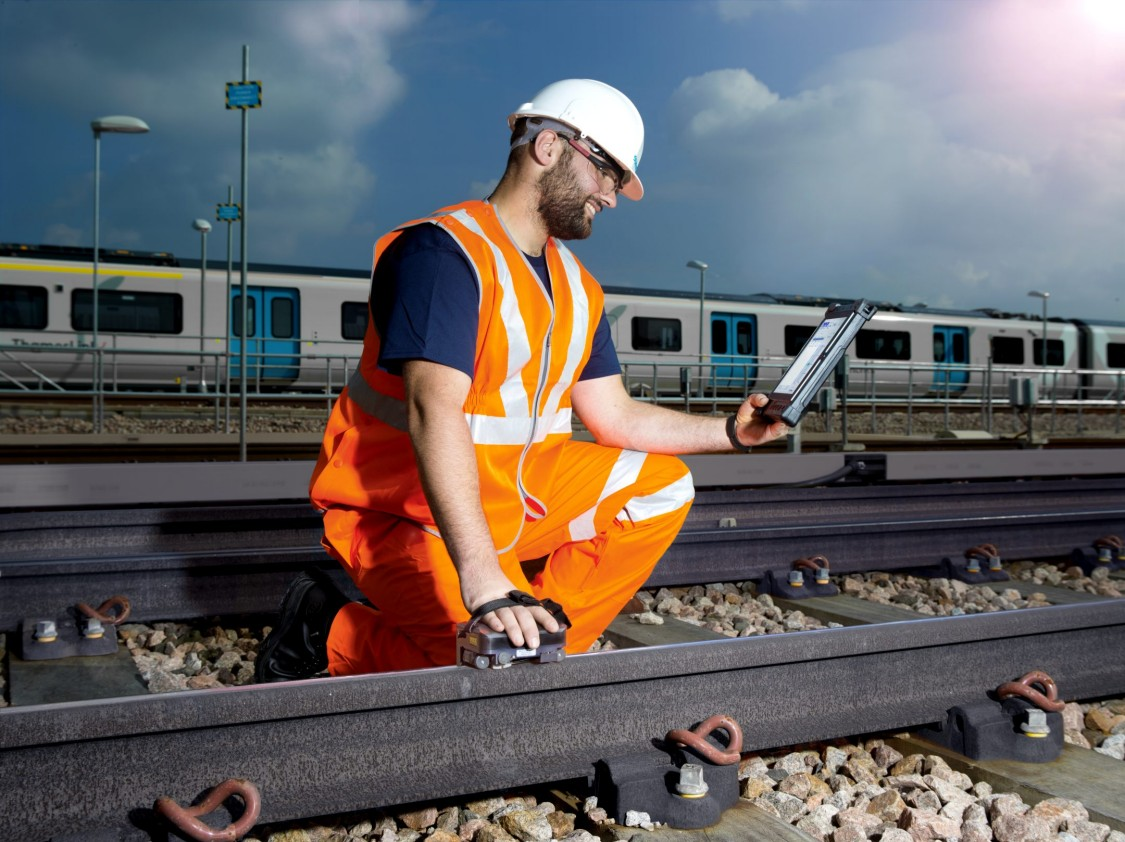 Man servicing a rail track with iPad in his hand