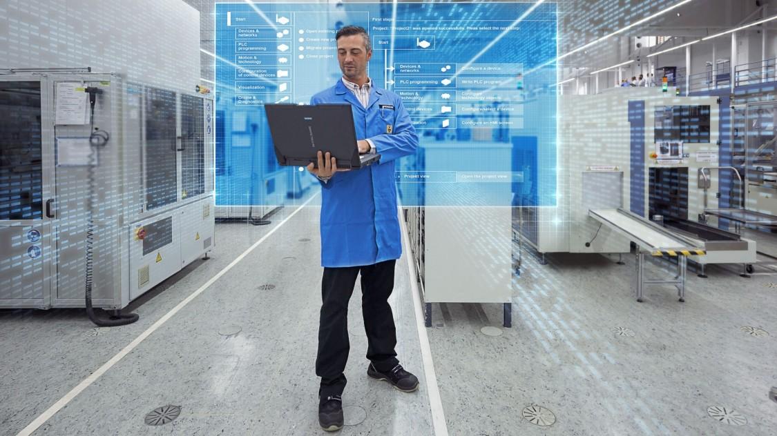 engenheiro de automação está em uma sala industrial olhando um notebook em suas mãos
