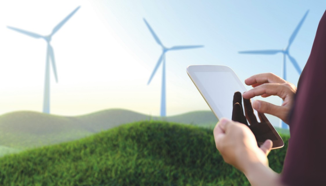 An engineer using a tablet to operate the wind turbine.