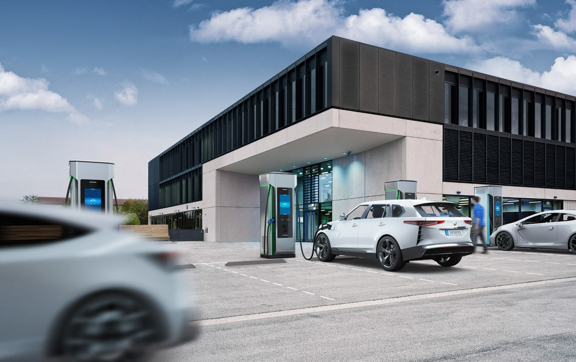 Image of a DC charging station in a modern commercial building – one electric car is charging, another is moving away