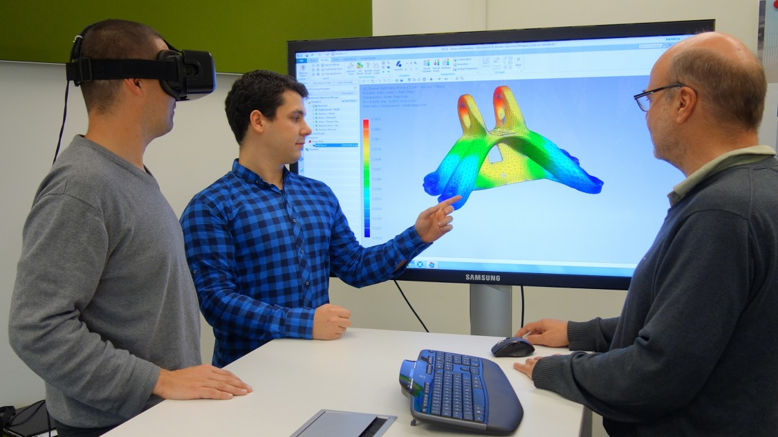Utz Wever (rechts) und zwei Kollegen aus der Vorfeldforschung für Simulationsinnovationen testen und diskutieren ihre Arbeitsergebnisse.