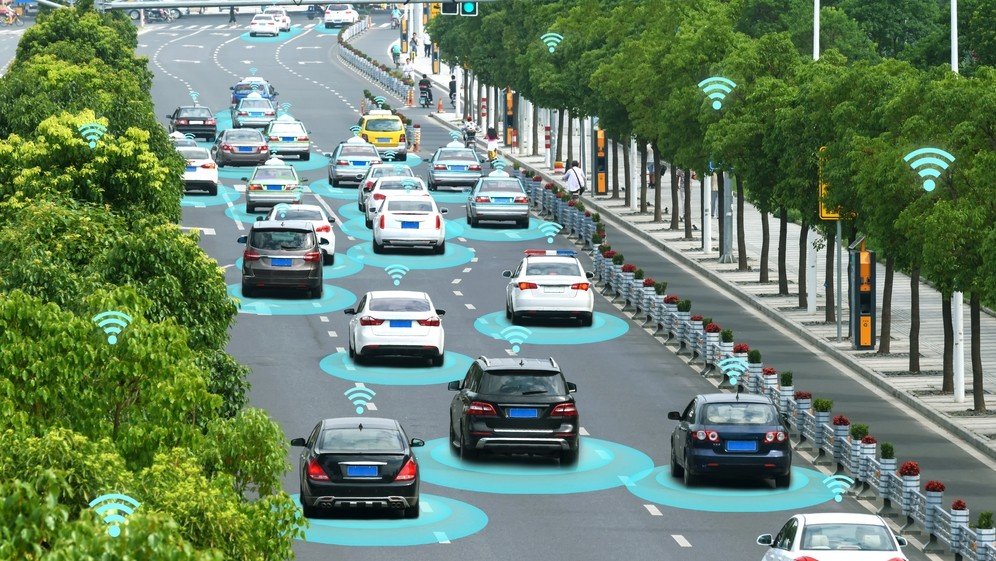Many connected cars driving on a motorway, communicating with infrstructure