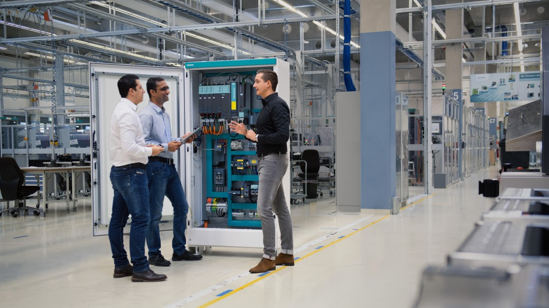 Three men talking in front of a control panel.