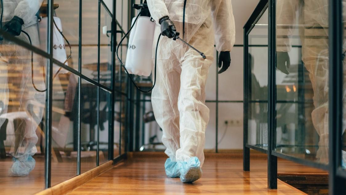 Un homme en tenue de protection décontamine un sol de bureau.