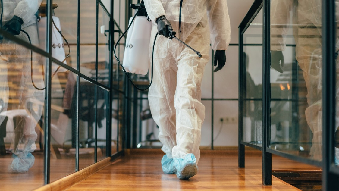 Man in protective suit is decontaminating an office floor.