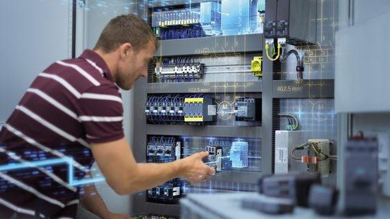 Mann vor einem Schaltschrank, der eine Komponente im Schaltschrank bedient.