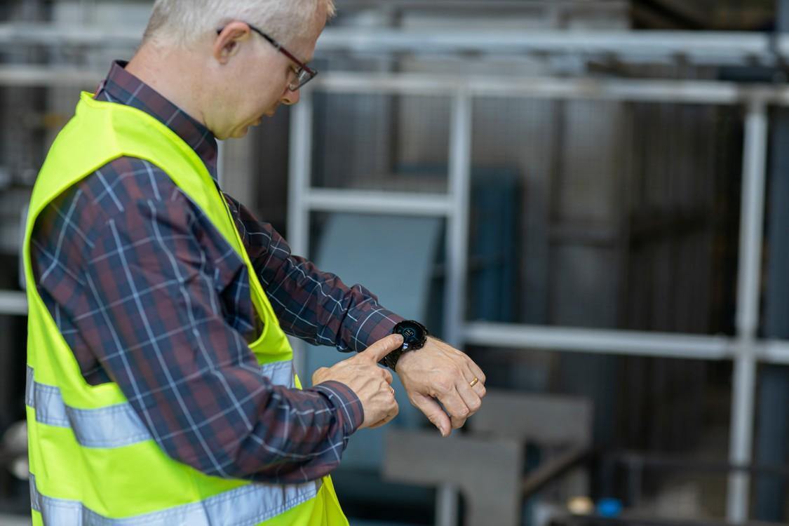 Ein Techniker prüft seine Smartwatch, auf der eine Push-Nachricht zum Anlagenzustand angekommen ist