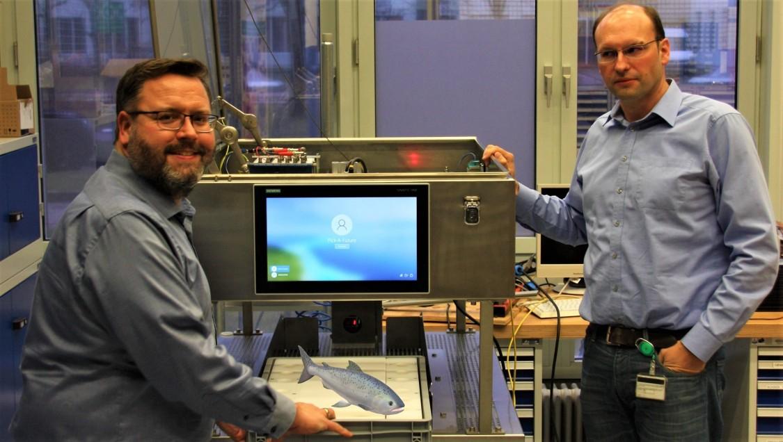 """In diesem Fall nur ein """"digitaler"""" Fisch zur Illustration: Alexander Gigler (l) und Sven Dudeck (r) vor dem Laboraufbau in München"""