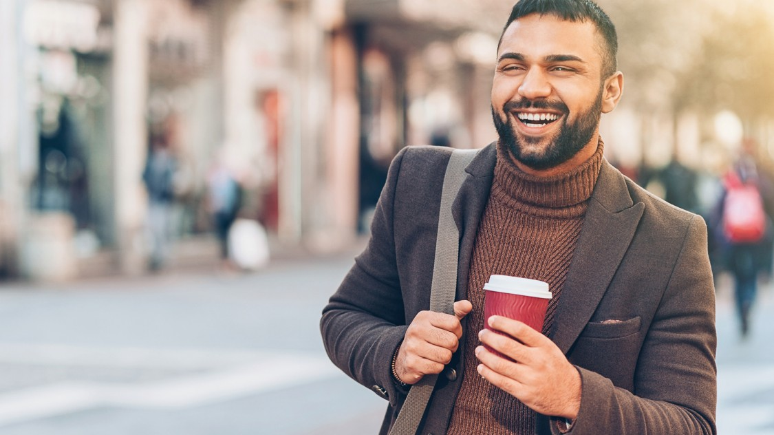 A man with a beard in his early 30s is walking in a pedestrian zone. He holds a coffee cup and is carrying a large shoulder bag.
