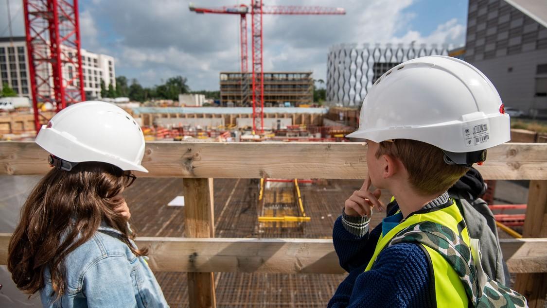 Zwei Schulkinder der Metropolitan School Frankfurt mit Blick auf die The Move Baustelle in Gateway Gardens