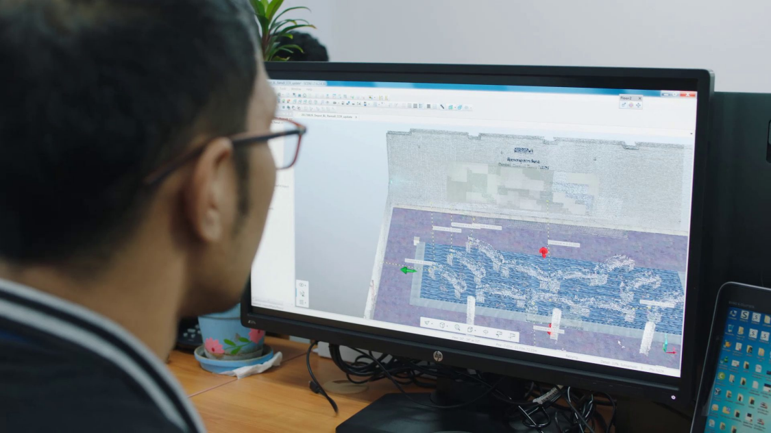 Man looking at a 3D-Model of a Operation Control Center in his computer