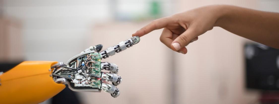 uma mão robôtica tocando um dedo de uma mão humana