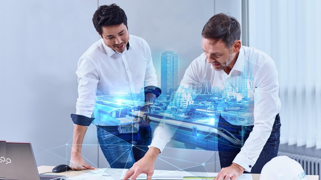 Zwei Projektmanager blicken auf den Zeitplan eines Bahnsystems und visualisieren das fertige Projekt