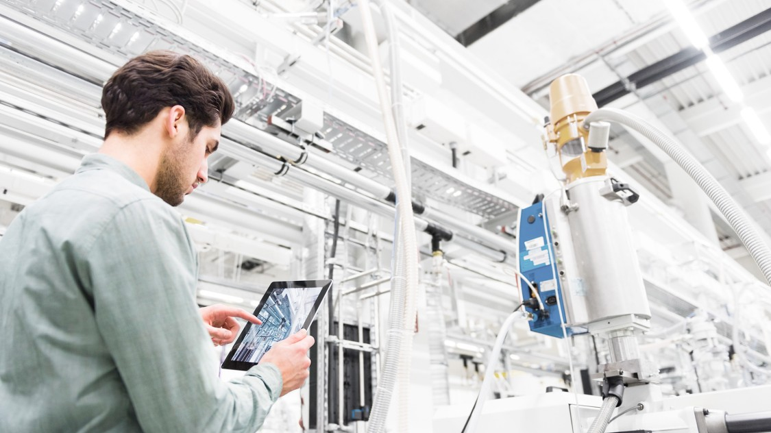 Specialist in a manufacturing plant checks plant data on his iPad