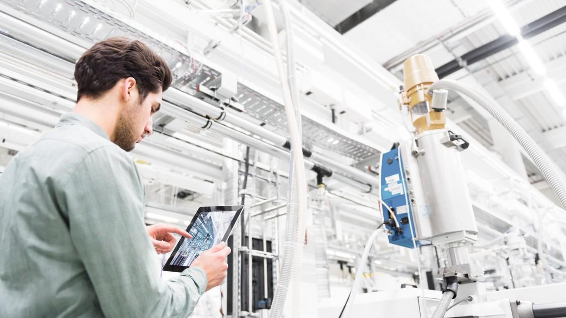 Spezialist in einer Fertigungsanlage kontrolliert Anlagendaten an seinem iPad