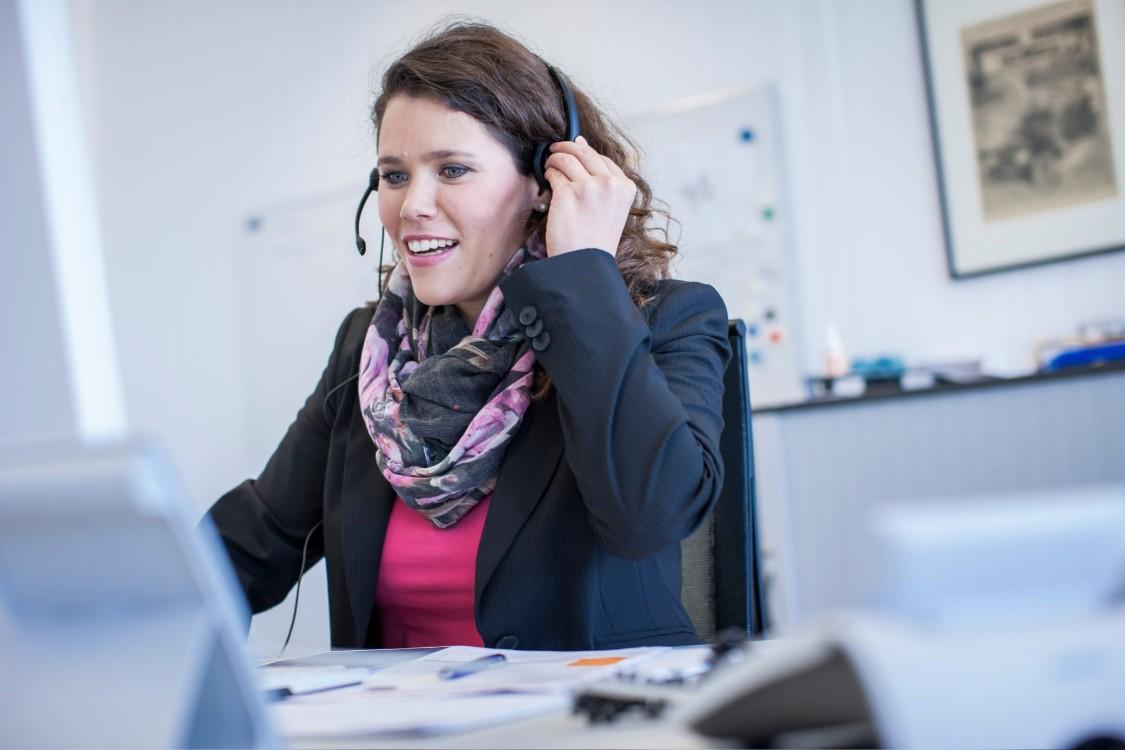Christina sitzt mit einem Headset am Schreibtisch