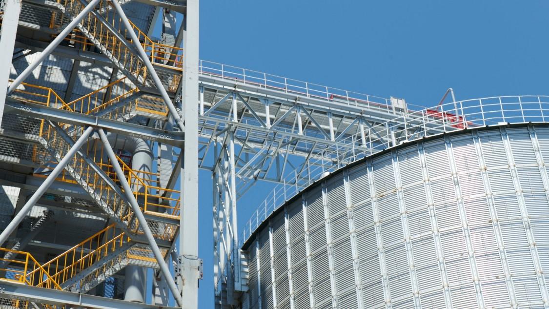 Perspektivisch von unten fotografiertes Tanklager in der rechten Bildhälfte und links einem Zugang wie ein Treppenaus der Bioproduktionsanlage von Cathay