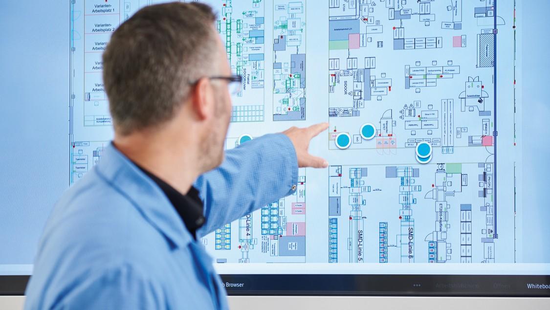 Ein Mann zeigt auf einen Monitor mit einer digitalen Karte einer Fabrik