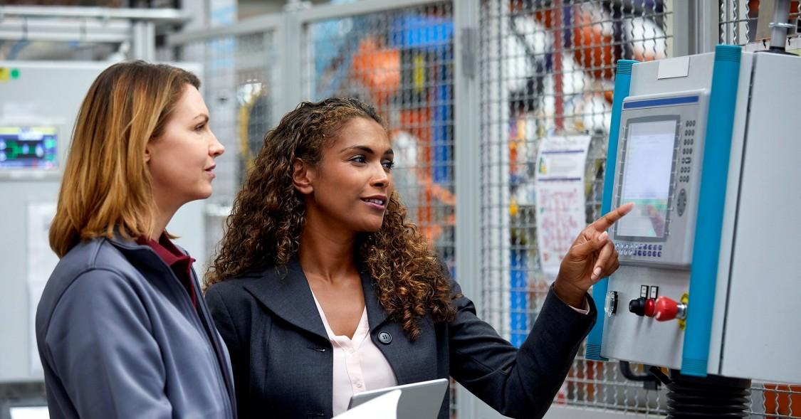 Zwei weibliche IngenieurInnen, die ein Steuerelement überprüfen