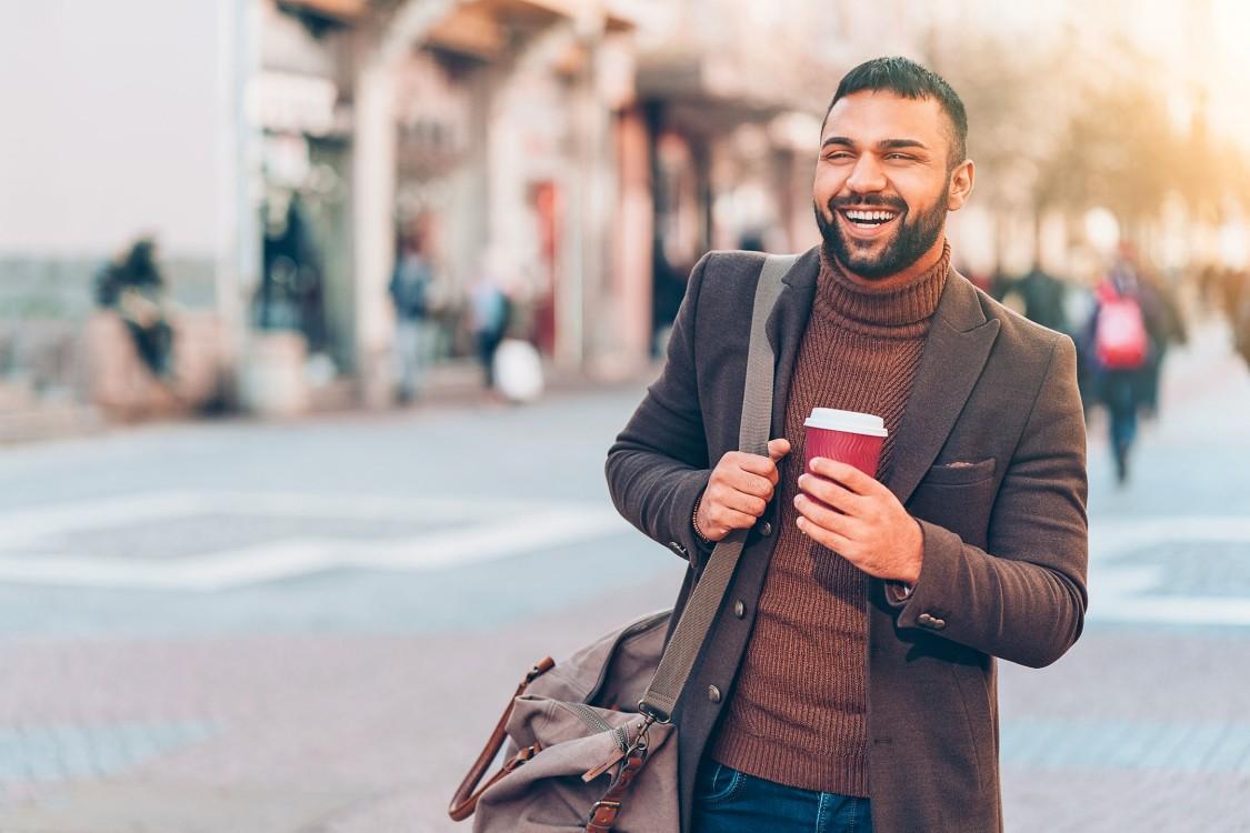 Ein Mann mit Bart Anfang 30 läuft in einer Fußgängerzone. Er trägt einen Kaffeebecher und eine große Umhängetasche.