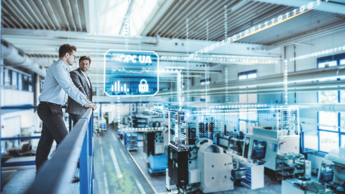 Two men stand on a balustrade overlooking an automation system that exchanges data with the cloud in a stylized way.